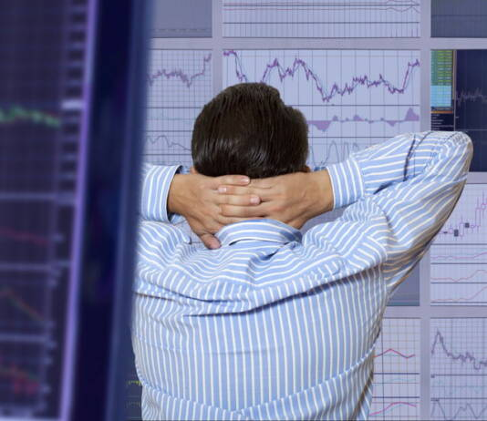 Mężczyzna obserwuje wykresy i ocenia ryzyko inwestowania w papiery wartościowe